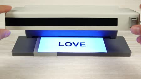 slova : The concept of love and hate. A detector with ultraviolet light changes the word love to hate.