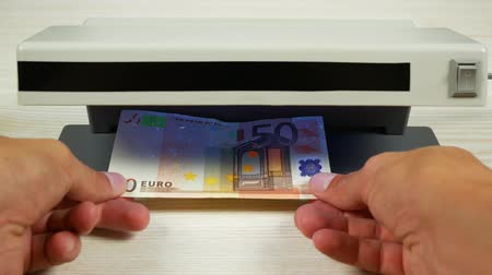 forgery : Authentication of money on the detector. Banknote denomination of 50 euros under the lamp of the detector