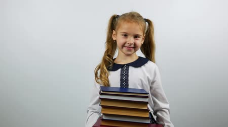 schoolbook : Portrait of school child in uniform. A stack of books in the hands of a schoolgirl.