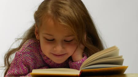 erudite : Young girl smiling while reading book. Front view of cute teen lying with opened book Stock Footage
