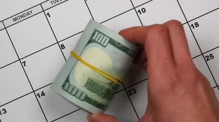 imposition : Paper calendar reminder about paying taxes. The hand puts dollars next to the word taxes