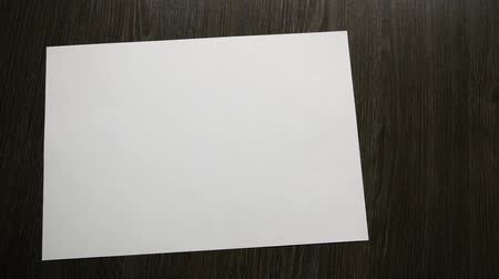 White paper for notes falls on a dark wooden table. Slow motion Stock Footage