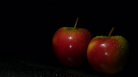 Crispy, juicy apples in splashes of water in darkness. Stock Footage