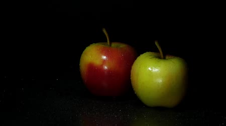 Two apples on a dark background. A drop of water flows down the apple.