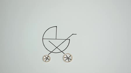 Baby carriage with wheels from wedding rings. Stop motion Stock Footage