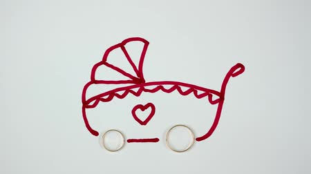 отцовство : Wedding rings turn into the wheels of a pram. Family concept Стоковые видеозаписи