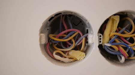Three horizontal openings with wires in the wall for sockets.