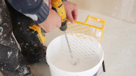 The worker with electric drill mixes the paint in a bucket Stock Footage