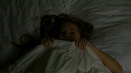 The child frightenedly hides under the blanket at night