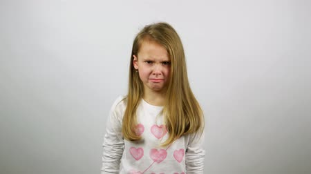 displeasure : The young girl looking angry and begins to cry. A frustrated child crying looking straight Stock Footage