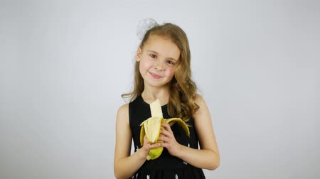 muz : Portrait of cute child eating banana. Studio shot