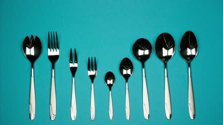основное блюдо : Forks and spoons from small to large in one row on blue background