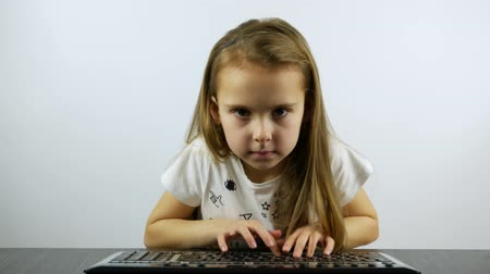 A concentrated girl vigorously presses the button of the keyboard and rejoices in victory