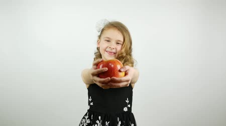 достигать : A curly girl holds out an apple to the camera. A beautiful child offering a large red apple