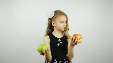 sağlamak : Very beautiful girl holds a red and green apple in hands. Selects and offers a green apple