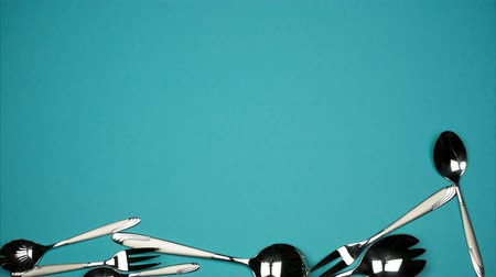 Falling spoons and forks on the blue background Stock Footage