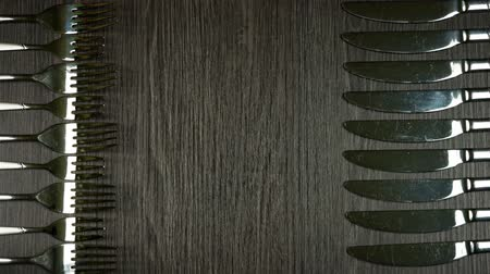 Forks and knives appear on the sides on dark wooden background with copyspace. Stop motion animation