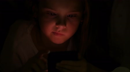 Cute girl under a blanket in the light of a smartphone
