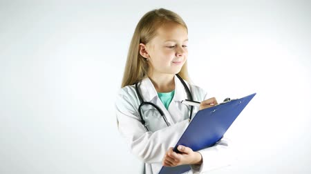 Portrait of a girl doctor. Child wearing doctors gown with stethoscope writting the recipe