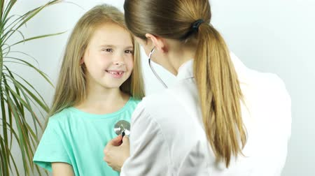A female doctor hearing heartbeat of cute young girl. Review of a child in a pediatrician