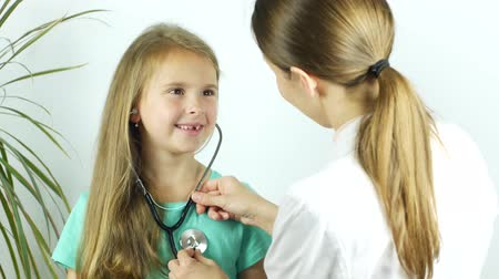 self examination : A girl listens to a heartbeat with a stethoscope