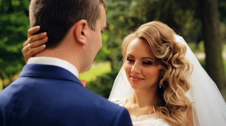 weddings : Bride and groom in love looking at each other at beautiful green park shot in slow motion  close up