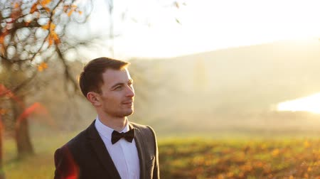 inspiradora : stylish brunette smiling groom in a suit with a brown bow holds  walking autumn park