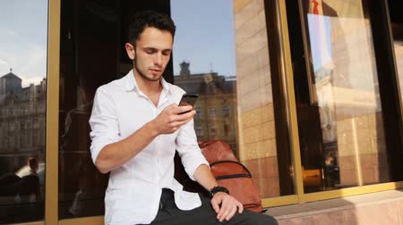использование : Young caucasian man in white shirt typing on his smartphone outdoors