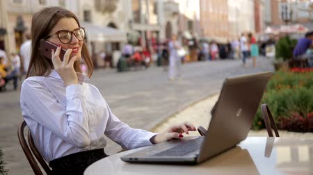 zawód : Smiling attractive lady with red lips is talking on her cell phone and using her laptop Wideo