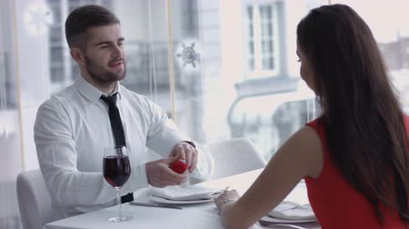 обещание : Man produces ring and asks woman to marry him - she accepts,  Marriage Proposal - A man gives a ring to a woman proposing marriage. She surprises and smiles.   Indoors, restaurant, romantic dinner