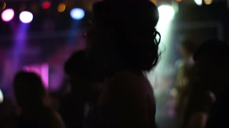 boate : Young handsome lady worn on fancy dress is dancing at nightclub  strobe and colorful lights on the background.