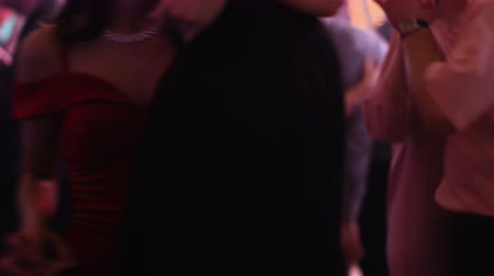 casal heterossexual : Beautiful heterosexual couple with no faces slow dancing at a club. Man keeps his female partner in a sensual dance. Medium shot. Stock Footage
