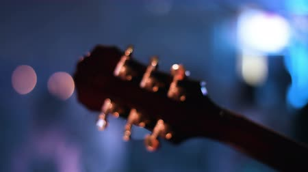 headstock : Detail footage of guitar headstock  which is played by musician on a concert. People dancing on a blurred background.