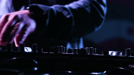 loud music : Close-up footage of a male DJs  hands mixing music at a party by using his control desk,artist is using his instrument for playing music at a stage.