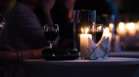 vacsora : Close-up footage of elegantly decorated table at restaurant,female visitor holding a glass of red wine, fancy black clutch bag is near.