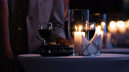 coquetel : Close-up footage of elegantly decorated table at restaurant, woman holding a glass of red wine, fancy black clutch bag is near. Man brings a plate with food and have a drink.