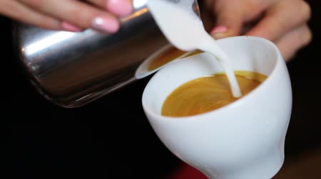 sztuka : hands of barista making latte or cappuccino coffee pouring milk making latte art. Wideo