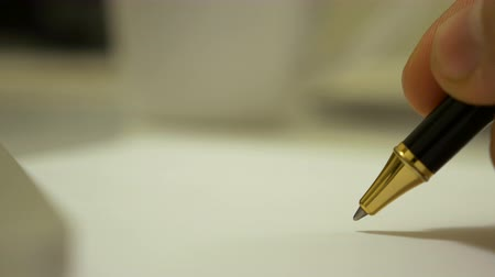 boletim : Macro footage of a black ball pen starting to write on a paper by a man hand.