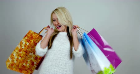 pulóver : Young blonde woman appears with colorful shopping packages in her hand, she smiles and then fades away. Stock mozgókép