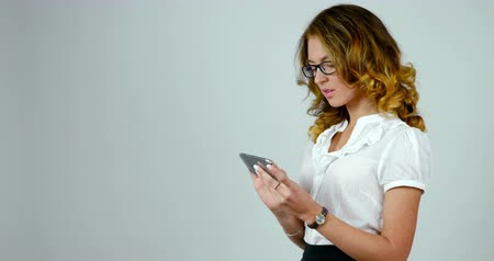 boss : Young attractive woman uses smartphone, footage from studio , business woman isolated on white background