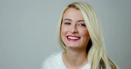 sarışın : Close-up studio footage of an attractive blonde girl laughs. Stok Video