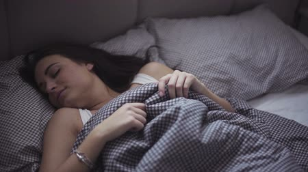 sen : Slow motion footage of an attractive caucasian girl who is easy waking up in her cozy bed. Wideo