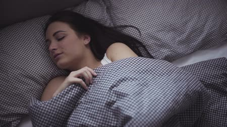 napping : Female in her 20s wakes up in the morning in a bed, girl is stretching herself after sleeping. Stock Footage