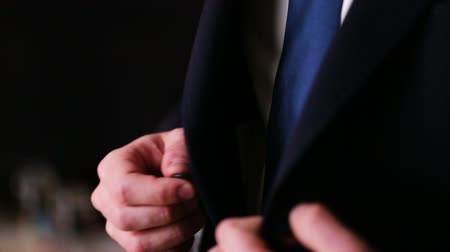 üzleti öltöny : Close up of a groom preparing for his wedding and buttoning up black fashionable  suit.