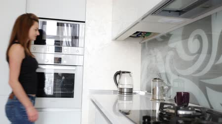 kitchen furniture : Beautiful woman turning on modern glass electric kettle on the fancy contemporary kitchen.