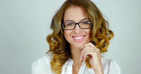 espetáculos : Close-up portrait of a young female model with eyeglasses is posing and smiling in studio.