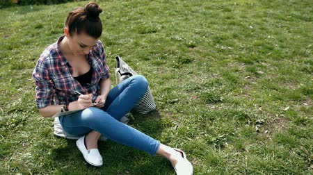 pléd : Young woman in casual clothes writing in her journal sitting on grass in the park
