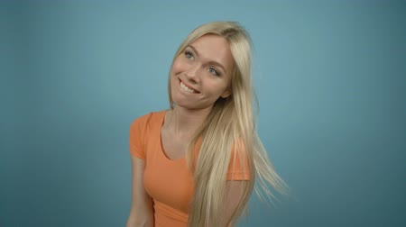 coquettish : Beautiful playful laughing woman with long blonde hair posing in orange T-shirt against a blue background