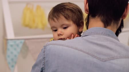 paternal : Young father is holding his sleepy baby son over his shoulder carrying him to the bed Stock Footage