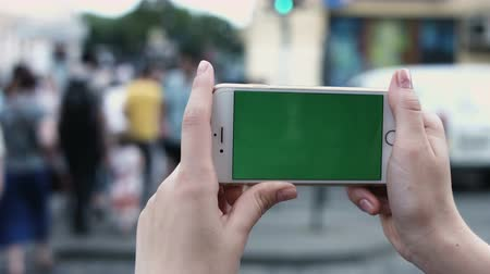 phablet : Teen Girl is Using Smartphone with Green Screen in Landscape Mode at Evening. Casual Lifestyle.  Shot on RED Cinema Camera in 4K?  ProRes codec - Great for editing, color correction and grading. Stock Footage